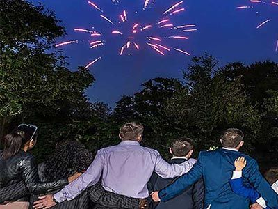 family arm-in-arm watching fireworks