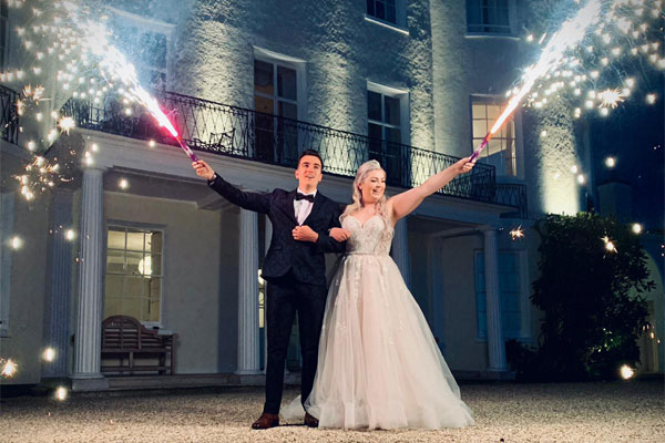 Wedding Couple hold coloured flares just as the turn to silver sparks
